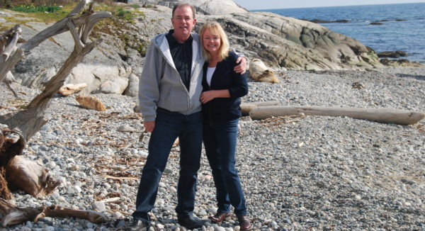 couple on beach who have downsize